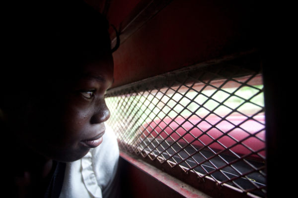 A young girl stares through the grated window of a tap tap in Haiti