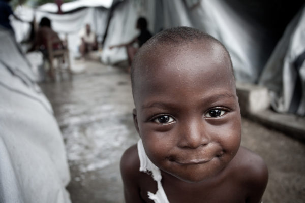 A young boy smiles despite the conditions in a tent city in Port-au-Prince, just months after the January 2010 earthquake.