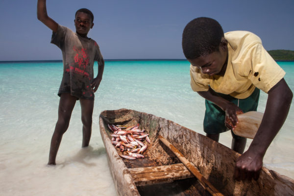 A boy empties the water out of a boat on a beach on Petit Cayemite Island in Haiti