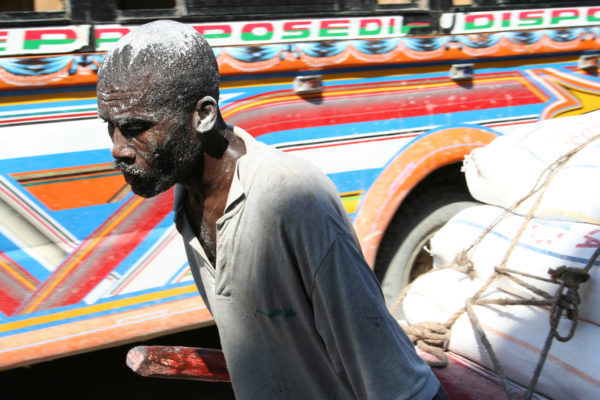 A limestone miner splattered with limestone hauls a load through the bustling streets of Jeremie, southern Haiti